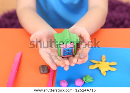 Child's hands holding hand-made plasticine house over desk