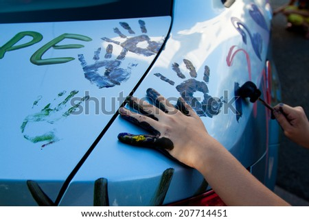 child\'s hands in paint, making a mark on the hood of the car, paint the car