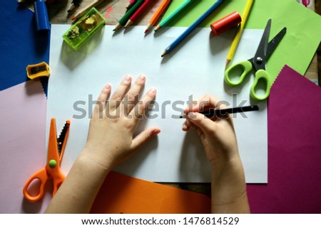 Child's hands on the table with pencils and Colored paper. The girl writes in pencil in a notebook. Back to school