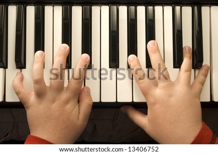 Child's hands playing a piano keyboard