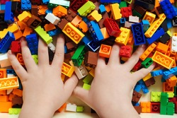 Child's hands takes many plastic blocks. Closeup of child's hand with colorful plastic blocks. Little boy playing with construction toys at home, in kindergaten or preschool. Creative games for kids.