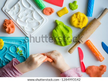 Child's hands with colorful clay. Child playing and creating vagetables from play dough. Girl molding modeling clay. Homemade clay.