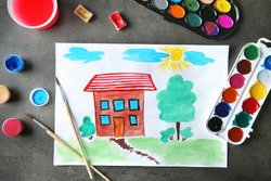 Child's painting of house on table