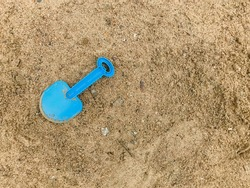 Child's shoulder blade on wet sand. Blue blade in sand on beach. Abandoned, forgotten toy shovel. Concept summer children's recreation after quarantine. Texture sand. Place for an inscription or logo