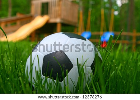 Child's soccer ball in front of a children's playground