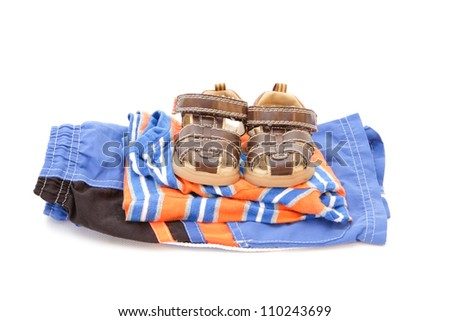 Child's summer clothing and sandals on a white background