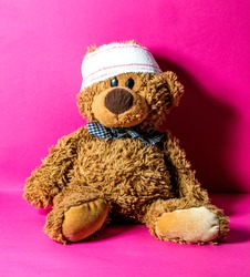 child's teddy bear with a head bandage for concept of domestic mishap and injury over nursing pink background