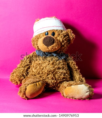 child's teddy bear with a head bandage for concept of domestic mishap and injury over nursing pink background  #1490976953