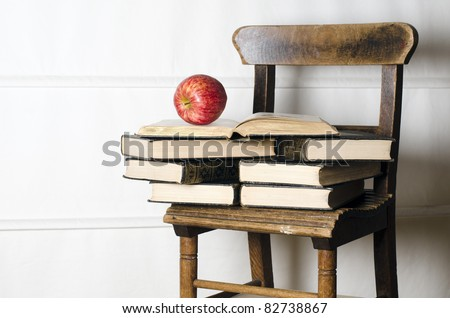 Child's vintage school chair supporting old books and apple. Education concept. - stock photo