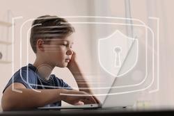 Child safety online. Little boy using laptop at home. Illustration of internet blocking app on foreground