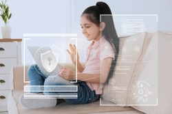 Child safety online. Little girl using laptop at home. Illustration of internet blocking app on foreground