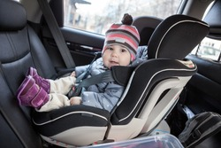 Child safety seat with smiling infant child is on back seat of car, a kid eight month old