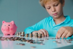 child saving money, boy put coins into piggy bank