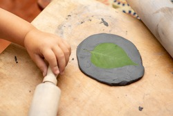 Child Sculpt Tree Leaf Print In A Black Clay.