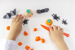Child sculpts pumpkin from dough on a white wooden background with. Top view. Concept of preparation to halloween in the kindergarten.