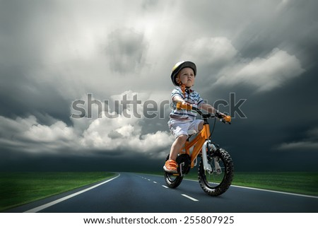 Child seating on the orange bicycle and travelling on the non-urban road under sky
