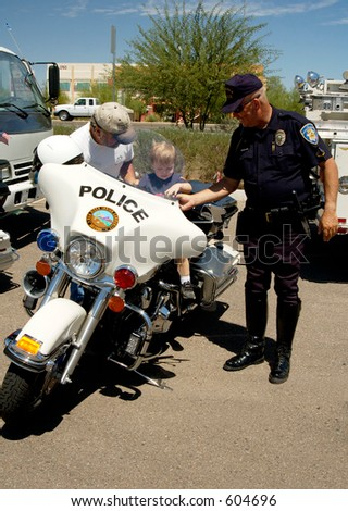 Child setting on a police motorcycle on display.