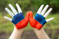 Child show hands painted in Russia flag colors walking outdoor. Day of Russian flag. Patriots patriotism citizens nationality. June 12. August 22 holiday. November 4