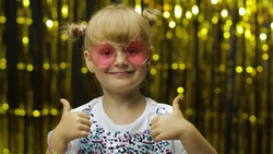 Child show thumbs up, smiling, looking at camera, demonstrating approval, satisfied with excellent result. Little fun blonde kid teen girl 4-5 years old in pink sunglasses posing on shiny background