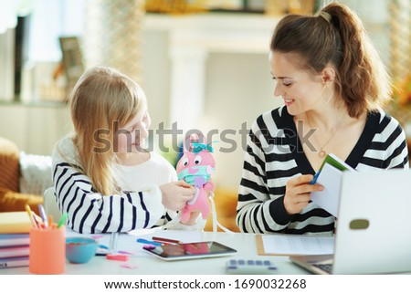 child showing mother pink toy rabbit in medical mask in temporary home office in the modern house in sunny day. Photo stock ©