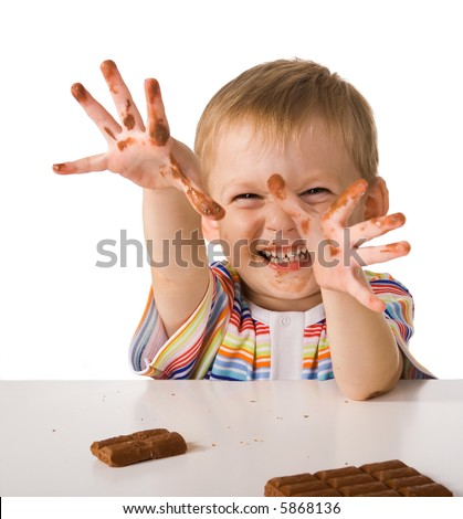 Child shows hands smeared by chocolate