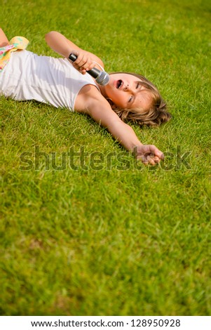 Child singing with microphone and lying on grass - outdoor lifestyle