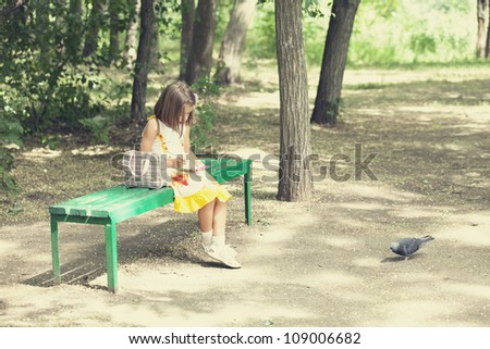 Child sit on the bench in the park.