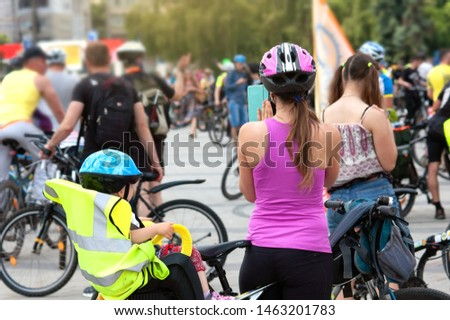 child sits in child's seat and bike security helmet with mother in bycicle competition, children sport equipment chairs and helmets for cycling concept