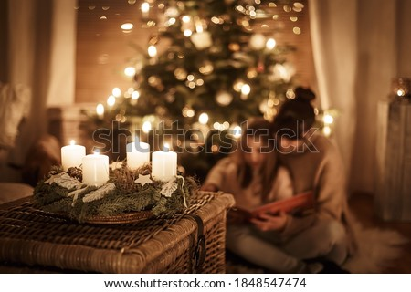 Child sits with mother in front of the Christmas tree and read a book together and look forward to X-Mas, advent wreath