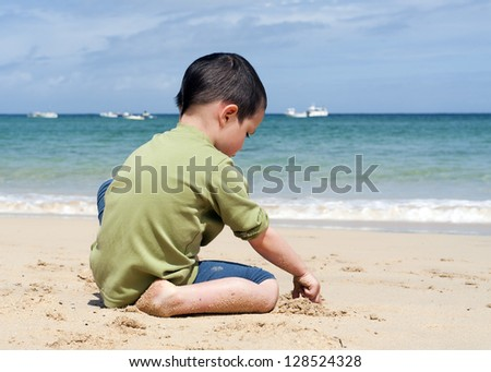 Child sitting on a beach, playing with a sand, clear blue turquoise sea with few boats or yacht on a horizon.