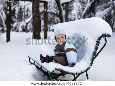 Child sitting on a bench in a winter park covered with much snow