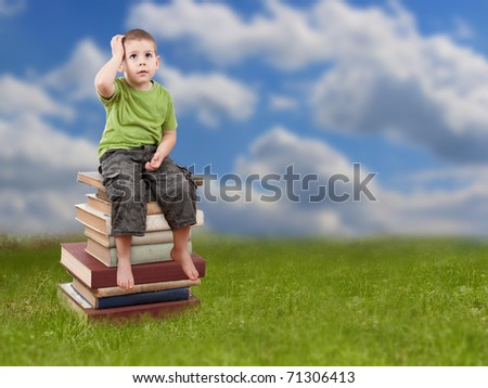 Child sitting on a stack of books and looking up, sky in background