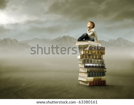 Child sitting on a stack of books in a desert