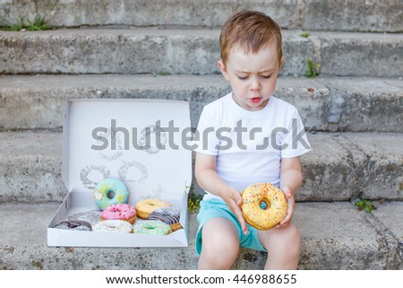 child sitting on the steps with a box of donuts. little boy playing with a donut. concept of junk food for kids - Shutterstock ID 446988655