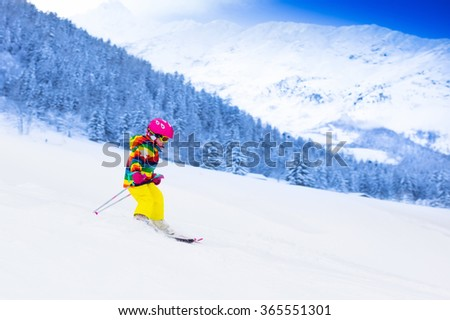 Child skiing in mountains. Active toddler kid with safety helmet, goggles and poles. Ski race for young children. Winter sport for family. Kids ski lesson in alpine school. Little skier racing in snow #365551301