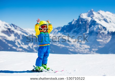Child skiing in mountains. Active toddler kid with safety helmet, goggles and poles. Ski race for young children. Winter sport for family. Kids ski lesson in alpine school. Little skier racing in snow #530710522