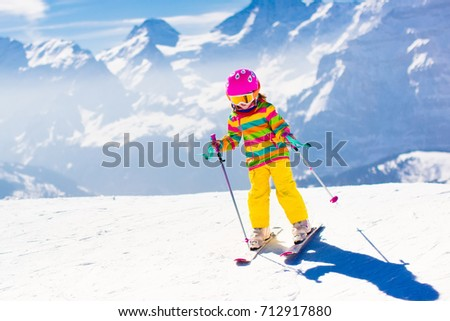 Child skiing in mountains. Active toddler kid with safety helmet, goggles and poles. Ski race for young children. Winter sport for family. Kids ski lesson in alpine school. Little skier racing in snow #712917880