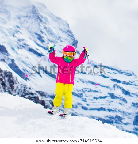 Child skiing in mountains. Active toddler kid with safety helmet, goggles and poles. Ski race for young children. Winter sport for family. Kids ski lesson in alpine school. Little skier racing in snow #714515524