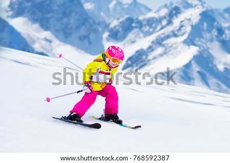 Child skiing in mountains. Active toddler kid with safety helmet, goggles and poles. Ski race for young children. Winter sport for family. Kids ski lesson in alpine school. Little skier racing in snow #768592387