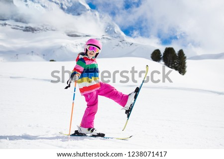 Child skiing in the mountains. Kid in ski school. Winter sport for kids. Family Christmas vacation in the Alps. Children learn downhill skiing. Alpine ski lesson for boy and girl. Outdoor snow fun. #1238071417