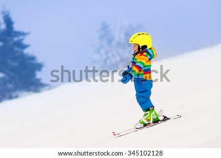 Child skiing in the mountains. Toddler kid in colorful suit and safety helmet learning to ski. Winter sport for family with young children. Kids ski lesson in alpine school. Snow fun for little skier.