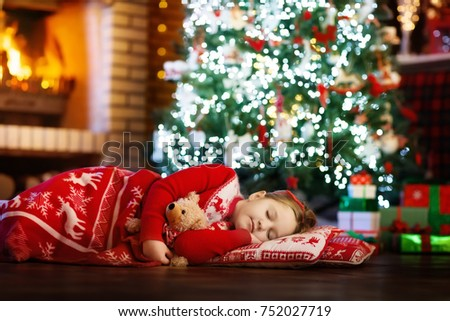 Child sleeping at fire place on Christmas eve under decorated tree. Family celebrating Christmas at home. Kids sleep. Presents at fire place. Little girl under blanket in winter holidays pajamas.
