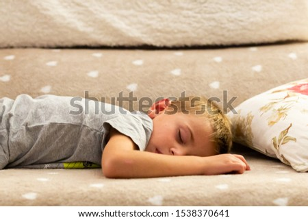 child sleeping peacefully on a couch with hearts. Adorable and innocent concept #1538370641