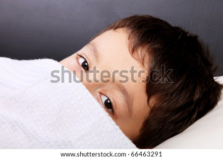 Child slept with the blanket in the face, looking at camera