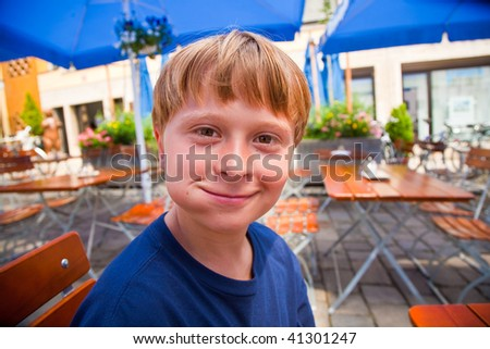 child smiles with full mouth and looks boldfaced