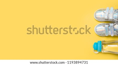 Child sneackers and bottle of water on yellow background. Top view, flat lay. Copyspace for text. Children healty lifestyle concept. #1193894731