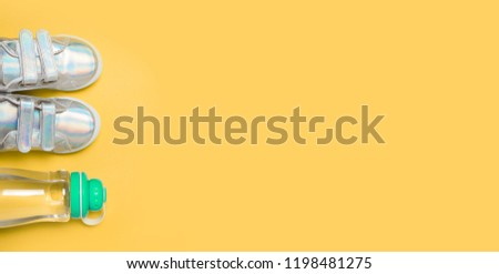 Child sneackers and bottle of water on yellow background. Top view, flat lay. Copyspace for text. Children healty lifestyle concept. #1198481275