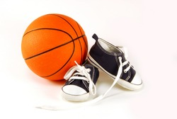 child sneakers and a basketball on white background