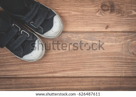 Child sneakers on wooden background. Fashion Children's shoes on a beach floor. Wood boardwalk. Top view. Style kids.