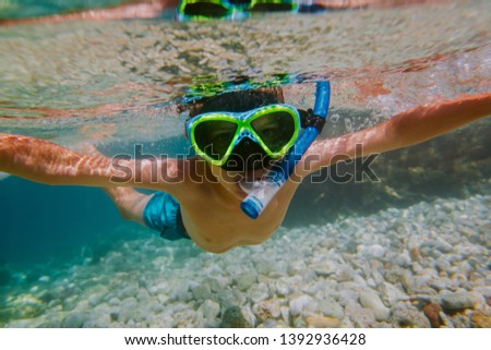 Child snorkeling in shallow sea. Young boy wearing diving mask and snorkel looking into camera underwater. #1392936428